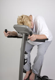 picture of exercise bike  - tired woman on exercise bike after workout - JPG