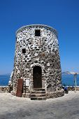 An old stone tower on the seafront at Mandraki on the Greek island of Nisyros.