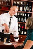 Wine bar professional waiter serve glass senior woman smiling