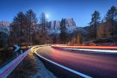Blurred Car Headlights On Winding Road At Night In Autumn. Landscape With Asphalt Road, Light Trails poster