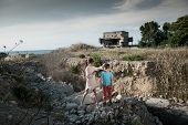 Thin Little Girl Refugee Soothe Her Small Brother On Ruins Of Demolished Building In War Zone poster
