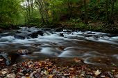 Long Exposure Of The River Flowing Into Crook Pool At Watersmeet In Devon poster