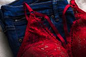 Woman Sexual Red Lingerie And Jeans On White Background Top View. Copy Space. Beauty, Shopping, Fash poster