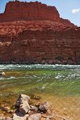 Cold green water of the Colorado River in the red rocks of the desert
