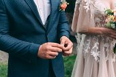 Wedding Rings. Selective Focus. Close-up. The Groom Wears The Wedding Ring To The Bride During The S poster