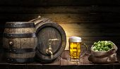Beer mug and small keg of beer on the wooden table. Craft brewery. poster