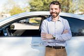 Smiling Mid Adult Man Making Eye Contact While Standing Arms Crossed Near White Car poster