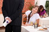 Man offering gift to woman in restaurant