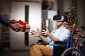 Cheerful Disable Man With Vr Goggle Sitting In Wheelchair And Stretching Arms To Take Giftbox With X poster
