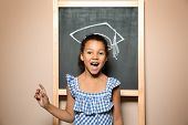 African-american Child Standing At Blackboard With Chalk Drawn Academic Cap. Education Concept poster