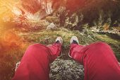 Male Traveler Legs Of A Traveler Sitting On A Rock Against A Cliff, Point Of View Shot. Travel Lifes poster