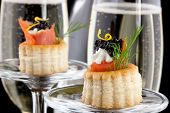 foto of canapes  - Closeup of black caviar on Creme Fraiche and smoked salmon canape and flutes of Champagne over black background - JPG