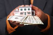 picture of american money  - African-American male hands holding a miniature house and American currency.