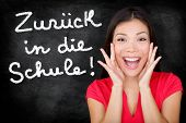 Zuruck in die Schule - German student screaming happy Back to School written in German on blackboard by female teacher. Smiling happy woman teaching German language or university student in college
