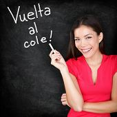 Vuelta al cole - Spanish teacher Back to School written in Spanish on blackboard by woman teacher holding chalk. Smiling happy woman teaching Spanish language or university student back in college.
