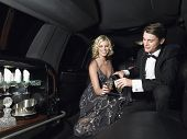stock photo of limousine  - Happy young glamorous couple enjoying champagne in limousine - JPG