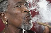 Closeup of a senior man exhaling cigar smoke against red background