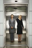 Two businesswomen standing together in office elevator