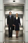 Front view of confident businessman and businesswoman standing together in elevator