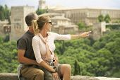 Middle aged couple sitting on wall with woman pointing at view; Granada Spain