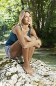 Full length of thoughtful young woman hugging knees while looking away by forest river