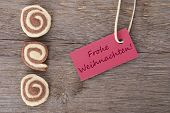 stock photo of weihnachten  - the german words Frohe Weihnachten which means merry christmas on a red tag with some cookies - JPG