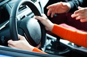 Driving School - Young woman steer a car with the steering wheel, maybe she has a driving test perha