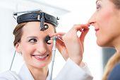 Médico - jovem consultor feminino ou otorrinolaringologista - com um paciente em sua prática, examinando o t