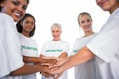 Team of female volunteers with hands together smiling at camera on white background