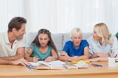 Parents helping their children doing their homework in living room