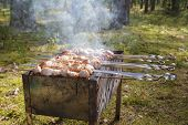 stock photo of brazier  - cooking pork shashlik on skewer in brazier outdoors - JPG