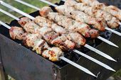 foto of brazier  - cooking pork shashlik on skewer in brazier outdoors - JPG