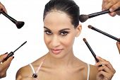 Sexy woman encircled by make up brushes on white background