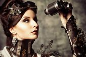 stock photo of binoculars  - Portrait of a beautiful steampunk woman looking through the binoculars over grunge background - JPG