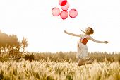 Pretty woman on a meadow jumping with red balloons