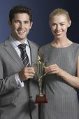 Portrait of a young businessman and woman holding a trophy against blue background