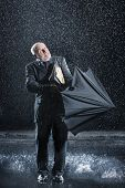 Middle aged businessman struggling to open umbrella during sudden rain