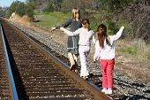 Girls Walking On Railroad Tracks