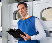 Portrait of happy young male helper writing on clipboard in laundry
