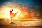 picture of  dancer  - Image of female ballet dancer against sunset background soaring above water waves - JPG