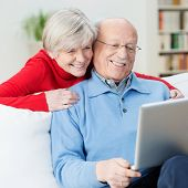 stock photo of wifes  - Amused senior couple using a laptop computer laughing as they look at something on the screen with the wife leaning over her husbands shoulder for a better look - JPG