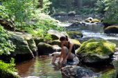 Woman Washing Her Feet In A Stream