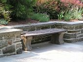 picture of fieldstone-wall  - wood and concrete bench set in a niche along a stone retaining wall with garden behind - JPG
