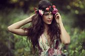 romantic beautiful woman summer portrait with wreath of flowers in vineyard