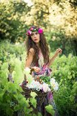 beautiful young woman summer portrait with wreath of flowers in hair and basket of flowers in hand o