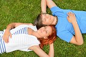 Young couple lying on grass closed eyes enjoy summertime top-view
