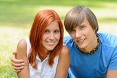 Teenage couple hugging enjoy summer day looking at camera