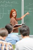 Mathematics student girl pointing on chalkboard looking at classmates