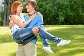 Teenage boyfriend carry girlfriend in his arms smiling in sunny park