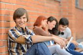 Student boy sitting by brick wall friends smiling in background